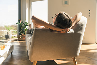 Relaxed young woman lying on couch - p300m2103873 by Uwe Umstätter