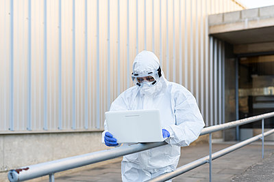 Female scientist wearing protective suit and mask and using laptop in front of the laboratory - p300m2170914 by Eloisa Ramos
