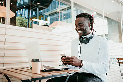Smiling creative businessman with laptop using mobile phone in cafe - p300m2242551 by Eva Blanco