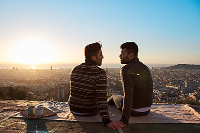 Gay couple looking at each other while sitting on observation point during sunrise, Bunkers del Carmel, Barcelona, Spain - p300m2257339 by Veam