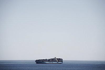Cargo Ship at Sea - p694m663681 by Maria K