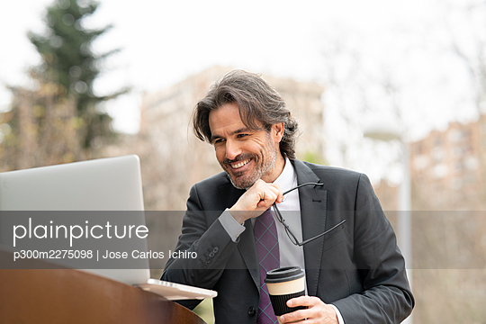 Happy businessman holding disposable coffee cup and eyeglasses while looking at laptop - p300m2275098 by Jose Carlos Ichiro