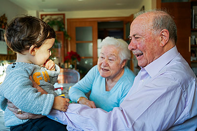 Great-grandparents playing with baby girl at home - p300m1562938 by Gemma Ferrando