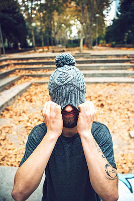 Young man covering face with knit hat while standing in park during autumn - p300m2206682 by klublu