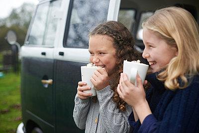 Girls drinking hot chocolate beside camper van - p429m2036686 by Peter Mason
