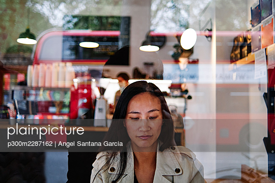 Mid adult woman sitting at cafe - p300m2287162 by Angel Santana Garcia