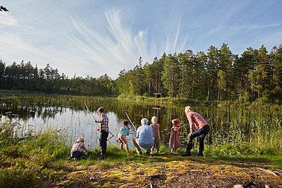 Grandparents and grandchildren fishing at sunny lakeside in woods - p1023m1172708 by Francis Pictures