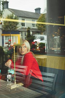 Woman looking through window while stirring coffee - p1315m2056352 by Wavebreak