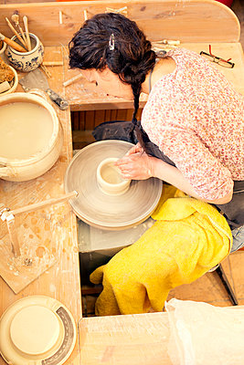 Potter in workshop working on potters wheel - p300m1022984f by Roman Märzinger