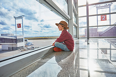 Boy sitting behind windowpane at the airport looking at airfield - p300m2070849 by Stefan Schütz