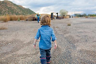Caucasian boy walking in gravel - p555m1410477 by Marc Romanelli
