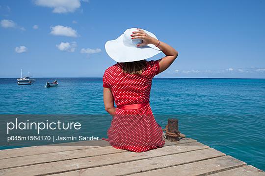 Frau sitzt am Meer - p045m1564170 von Jasmin Sander