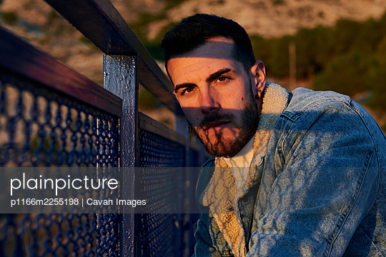 Handsome man in a jacket poses on a bridge at sunset - p1166m2255198 by Cavan Images