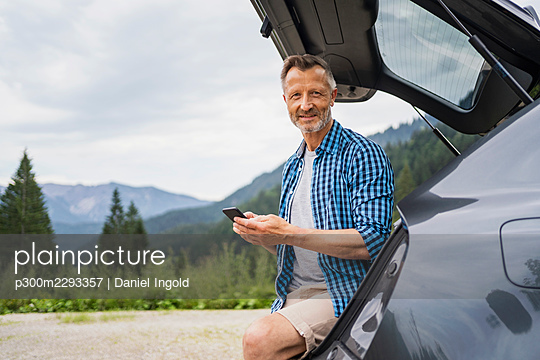 Mature man holding mobile phone while sitting in car trunk - p300m2293357 by Daniel Ingold