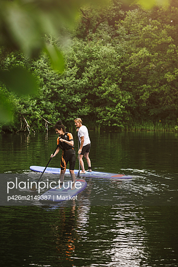 Senior man and woman learning paddleboarding in sea during SUP course - p426m2149387 by Maskot