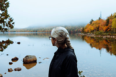 Side view of woman standing at lakeshore - p1166m1534458 by Cavan Images
