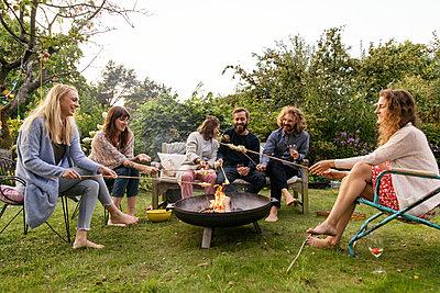 Roasting campfire bread - p788m2037431 by Lisa Krechting
