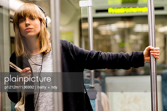Junge Frau unterwegs mit der S-Bahn - sitzend - p1212m1136992 von harry + lidy