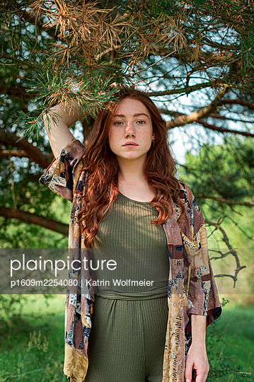 Young red-haired woman under a tree, portrait - p1609m2254080 by Katrin Wolfmeier