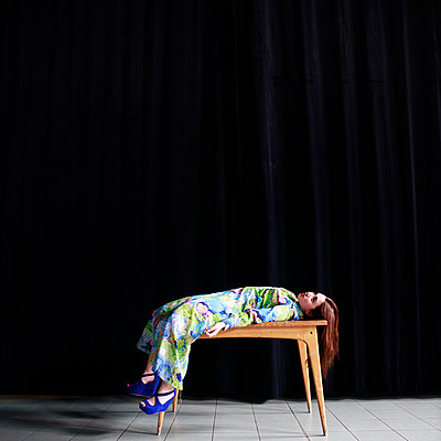 Woman lying on wooden table - p1105m2086547 by Virginie Plauchut