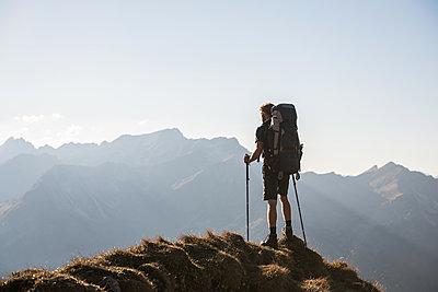 Junger Wanderer genießt Ausblick in den Bergen  - p1142m2056434 von Frithjof Kjer