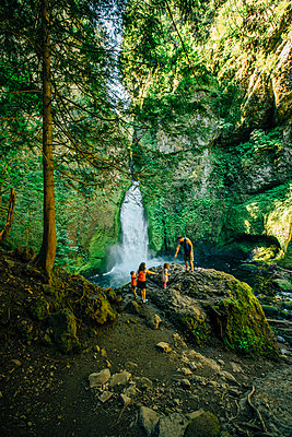 Family on rocks against waterfall at forest - p1166m1547040 by Cavan Images