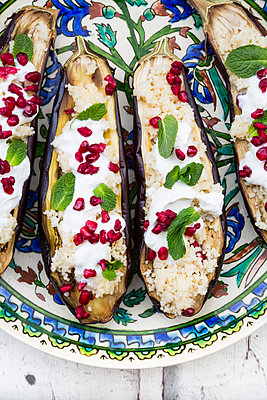 Filled aubergines with couscous, yogurt sauce, mint and pomegranate seeds - p300m2004233 von Larissa Veronesi