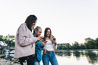 Three young women using cell phones at the riverside - p300m2023443 by Uwe Umstätter