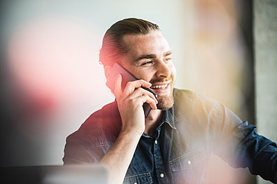Portrait of smiling young businessman on cell phone in office - p300m2043194 by Uwe Umstätter