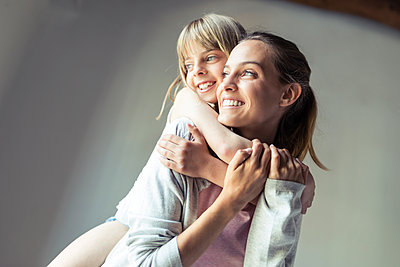 Mother and daughter playing at home, piggyback - p300m2114564 by Josep Suria