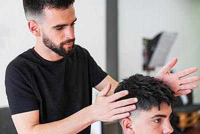 hairdresser combing a teenage boy, Matalascañas, Spain - p300m2275550 von Julio Rodriguez