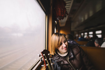 Smiling Caucasian woman with guitar sitting near window on train - p555m1301826 by Kateryna Soroka