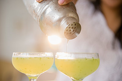 Pacific Islander woman pouring cocktails from shaker - p555m1413061 by JGI/Jamie Grill