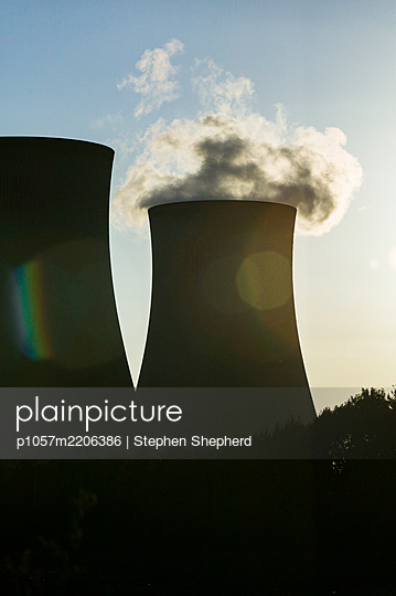 The sun looms over a power station throwing it into silhouette and backlighting the smoke, cables and pylons on the site. - p1057m2206386 by Stephen Shepherd