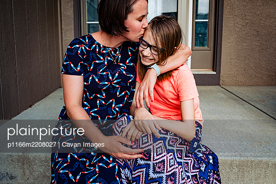 mom kissing daughter on front porch - p1166m2208027 by Cavan Images