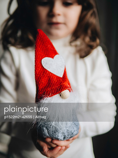 Girl holds christmas elf in hands - p1522m2142655 by Almag