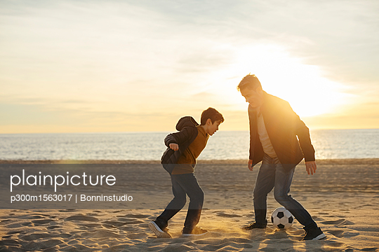 Father and son playing football on the beach at sunset - p300m1563017 by Bonninstudio