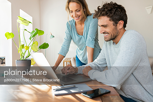 Cheerful couple working on laptop at home office - p300m2277586 by Steve Brookland