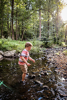 Boy playing in creek - p1019m2122604 by Stephen Carroll