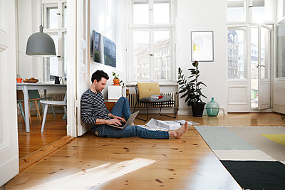Man sitting in foor, using laptop, working from home - p300m1588128 by Florian Küttler
