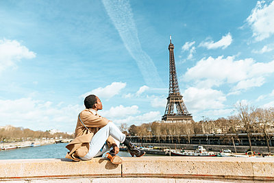France, Paris, Woman sitting on bridge over the river Seine looking at Eiffel tower - p300m2029795 by Kiko Jimenez