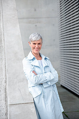 Portrait of content mature businesswoman leaning against wall wearing light blue trenchcoat - p300m2081358 by Viviane Wild