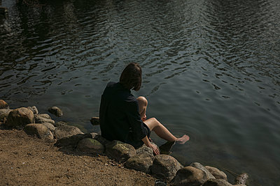 Woman sitting on the river banks - p600m2100047 by Laura Stevens