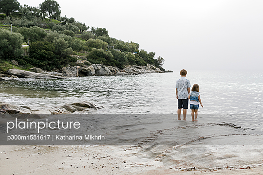 Greece, Chalkidiki, back view of brother and little sister standing at seaside - p300m1581617 von Katharina Mikhrin