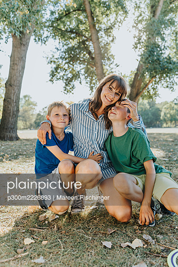 Happy mother embracing sons while kneeling in public park on sunny day - p300m2226893 by Mareen Fischinger