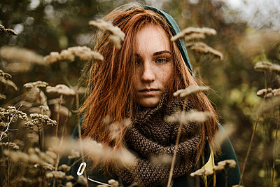 Thoughtful teenage girl with red head standing amidst plants - p1166m2113112 by Cavan Images
