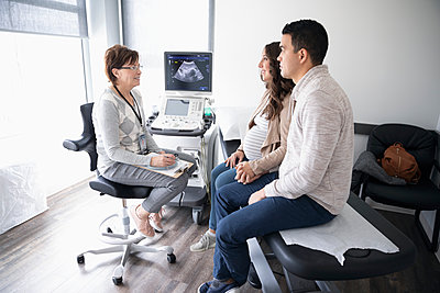 Female obstetrician talking with pregnant couple in clinic examination room - p1192m2040612 by Hero Images