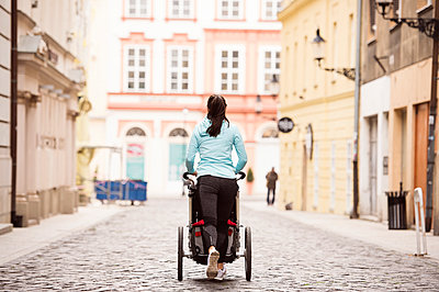 Woman running with stroller in the city - p300m1204993 by HalfPoint