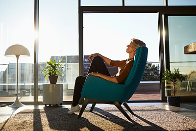 Woman sitting in armchair in sunlight with closed eyes - p300m2081356 by Rainer Berg