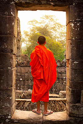 Novice monk in ruined building - p312m2161849 by Christopher Eriksson